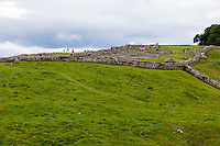 UK, England.  Housesteads Roman Fort. Hadrian's Wall enters upper right and continues lower right.  Foundations of soldiers' barracks are on the right, inside the fort's wall.