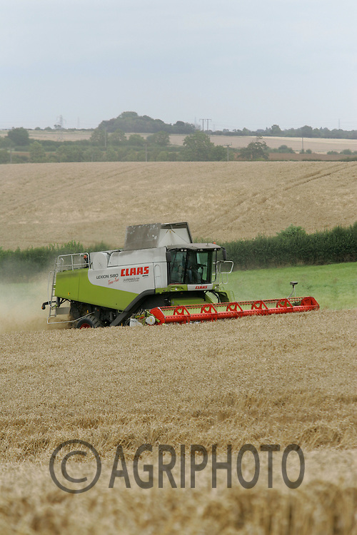 A combine harvester working in rolling countryside