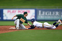 Siena Saints infielder Tyler Martis (1) tags out Jacob Cronenworth (2) after being picked off first on a stolen base attempt during the first game of a doubleheader against the Michigan Wolverines on February 27, 2015 at Tradition Field in St. Lucie, Florida.  Michigan defeated Siena 6-2.  (Mike Janes/Four Seam Images)