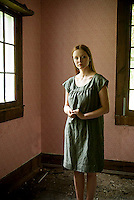 Young woman standing inside old dark wallpapered room