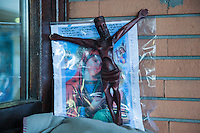 """Italy. Lombardy Region. Como. Homeless african migrants from Ethiopia living at the San Giovanni railway station. A wooden sculpture from Jesus Christ and a drawing from the Virgin Mary in a plastic folder. A crucifix (one) fixed to a cross"""") is an image of Jesus on the cross, as distinct from a bare cross. The representation of Jesus himself on the cross is referred  as the corpus. 10.08.2016 © 2016 Didier Ruef"""