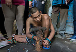 "5 April 2017, Surabaya,East Java,Indonesia: Febrianto, a 24 year old mental illness sufferer prepares to be released from the chains he has been shackled to a stake for the past two years in a goat shed next to his family in Pehwetan village, East Java. His mother Barokah, looks on (legs at left) as Indonesian Social Affairs Dept. workers cut the bonds and wash his emaciated body and apply first aid before putting him in a straight jacket and taking him to a facility in Malang for treatment. Febrianto is a patient in a program called ""E- Shackling"" which aims to free people suffering from mental illness, from the shackles that family often place them in to control them in the wake of a lack of treatment options and which will treat them and enter them in a data base allowing them to be traced before releasing them back to their families. Some people stay chained to a stake or in rooms for years by their families and not all families are willing to take their sick family members back. Picture by Graham Crouch/The Australian"