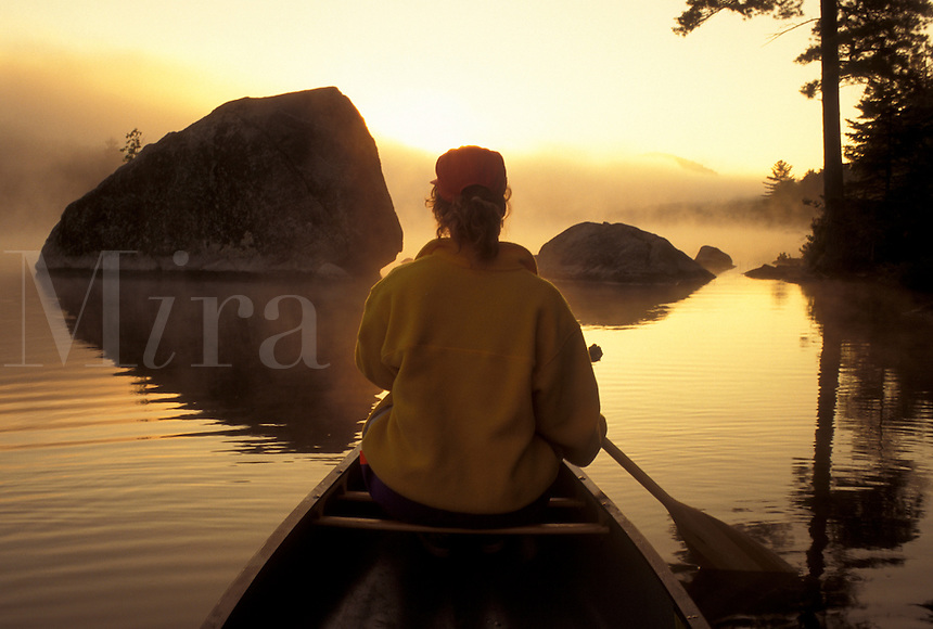 canoeing, canoe, Vermont, VT, Woman paddling a canoe on Kettle Pond through boulders in the fog in Groton State Forest.