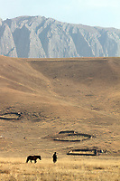 A Tibetan nomad and his horse on the Ganjia grasslands, near the town of Rebgong (Chinese name - Tongren) on the Qinghai-Tibetan Plateau. China.