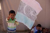 Tunisie RasDjir Camp UNHCR de refugies libyens a la frontiere entre Tunisie et Libye ....Tunisia Rasdjir UNHCR refugees camp  Tunisian and Libyan border  Campo profughi alla frontiera libica<br /> bambino con bandiera