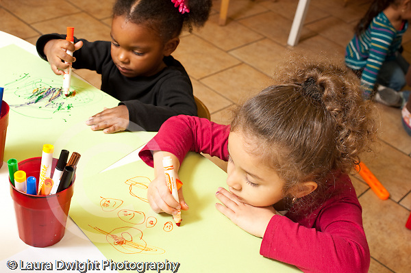 Education preschool 2-4 year olds art activity two girls drawing with markers younger girl holding marker in fist grip older girl using tripod grasp horizontal