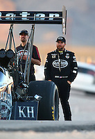 Mar 28, 2014; Las Vegas, NV, USA; A crew member with NHRA top fuel dragster driver Shawn Langdon (right) during qualifying for the Summitracing.com Nationals at The Strip at Las Vegas Motor Speedway. Mandatory Credit: Mark J. Rebilas-