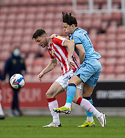 21st April 2021; Bet365 Stadium, Stoke, Staffordshire, England; English Football League Championship Football, Stoke City versus Coventry; Jordan Thompson of Stoke City is tackled by Callum O'Hare of Coventry City