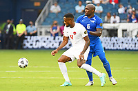 KANSASCITY, KS - JULY 11: Cyle Larin #17 of Canada watched by Jean-Sylvain Babin #6 of Martinique during a game between Canada and Martinique at Children's Mercy Park on July 11, 2021 in KansasCity, Kansas.