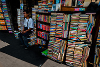 A Salvadoran bookseller sits in front of stacks of used books piled on the street in a secondhand bookshop in San Salvador, El Salvador, 10 April 2018. Large collections of worn-out books, mostly textbooks and educational paperbacks, are sold regularly in secondhand bookshops in the center of the city.