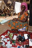 Senegal, Touba.  Woman Selling Mirrors in the Market.