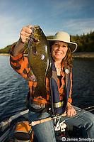 Woman holding a bass she caught fishing.