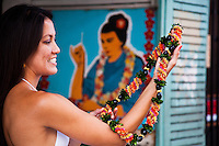 Young Hawaiian woman admires a cigar lei in front of a mural of a lei maker