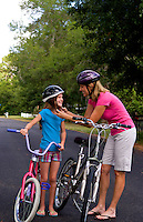 White mother and daughter having fun together outdoors with bikes and helmets for safety