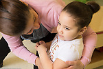 Education Preschool 4-5 year olds female teacher leaning into hold and talk to girl