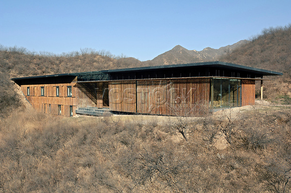 The Bamboo Wall House, by architect Kengo Kuma, wqas completed in 2002 as part of the multi-dwelling project Commune by the Great Wall near Beijing, conceived by developers Zhang Xin and Pan Shiyi. Requirements were to use local materials and conform to the topography, and Kuma chose to make maximum use of cheap bamboo normally used for construction scaffolding in China, to match the roughness of the surrounding landscape.