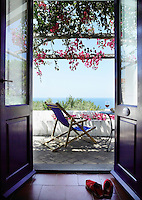 French windows open onto a secluded balcony shaded by vivid bougainvillea at the Hotel Sigmund in Italy