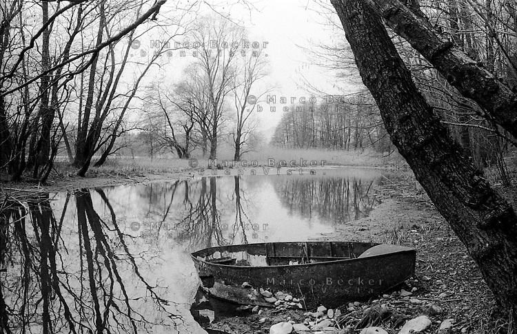Villa d'Adda (Bergamo), piccola barca in rovina abbandonata sulla sponda del fiume Adda --- Villa d'Adda (Bergamo), small boat in ruins abandoned on the Adda river bank