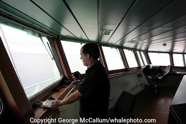 Whale researcher using angle board and microphone keyed GPS to report whale sighting from bridge of research vessel during Survey, Jan Mayen, North Atlantic