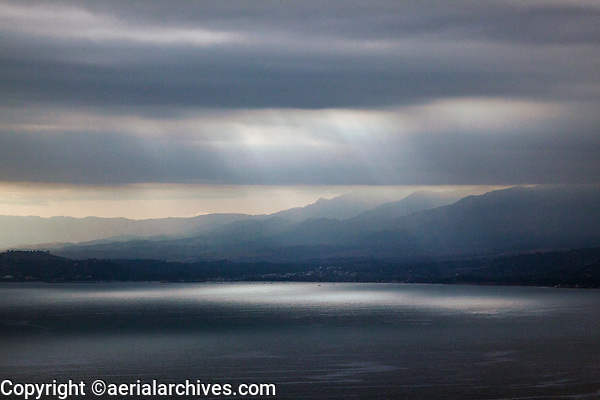 aerial photograph of light rays breaking through a layer of fog over the Pacific ocean at coastal mountains in Ventura County, California