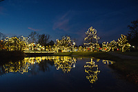 Christmas decorations and lights at Heritage Park in Westerville, Ohio, are reflected in the small pond in the park