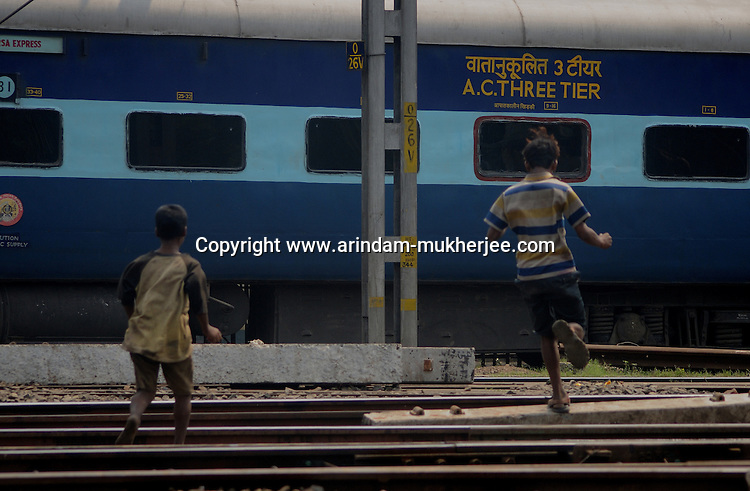 Alamgir and his mate Abhijit run along the railway track as an express enters the Sealdah station. The boys earn money by selling plastic botlles and goods they collect from the compartment when these empty of passengers. They eat left over food and buy drugs and dendrite adhesive with any money they get from pick pocketing. The Sealdah terminus station area is home to a thriving trade in narcotics. Calcutta, West Bengal, India. Arindam Mukherjee