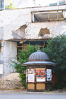 Building in Mostar damaged by the war and still not renovated. Ruined by bullet holes, mortar bomb shell grenade damage, very close to the beautifully renovated old town city centre. An old shopping centre on the Brace Fejica street. An abandoned news stand. Town of Mostar. Federation Bosne i Hercegovine. Bosnia Herzegovina, Europe.