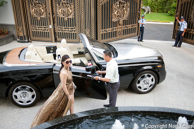 Former film actress and one of Vietnam's wealthiest women, Thuy Tien is the president of Imex Pan Pacific, a trading company that runs over 26 major businesses, including shopping malls, duty free fashion designer boutiques. Pictured here with her Rolls Royce, driver and gate security at the entrance of her high security riverside villa in Anphu, Saigon, a residential enclave with rich Vietnamese and expats.