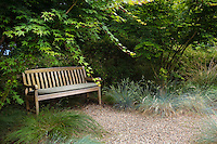 Garden bench in shade by gravel path with grasses, California garden