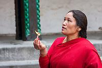 Nepal, Kathmandu.  Woman Worshiping at Hanuman Statue, Durbar Square.