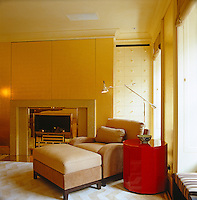 An armchair and matching foot stool in a corner of the contemporary bedroom beside the fireplace