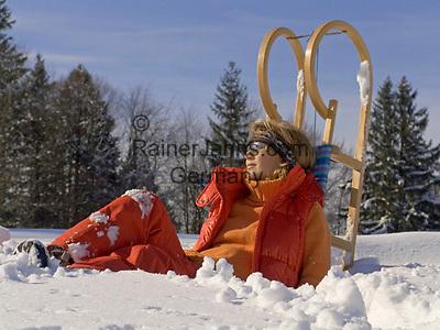 Deutschland, Frau mit Schlitten sitzt im Schnee | Germany, woman with sledge sitting in the snow