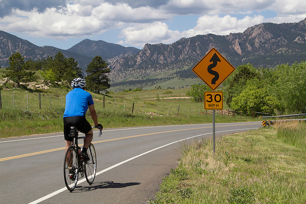 Man riding bike on mountain road in Boulder, Colorado .  John leads private photo tours in Boulder and throughout Colorado. Year-round.