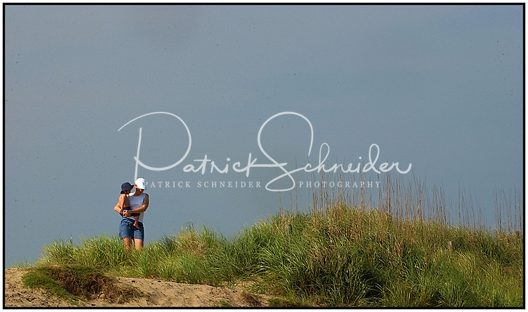 A mother walks carrying her son along a beach in the North Carolina Outer Banks near the Cape Hatteris Lighthouse. Photo is model released and can be used many places.