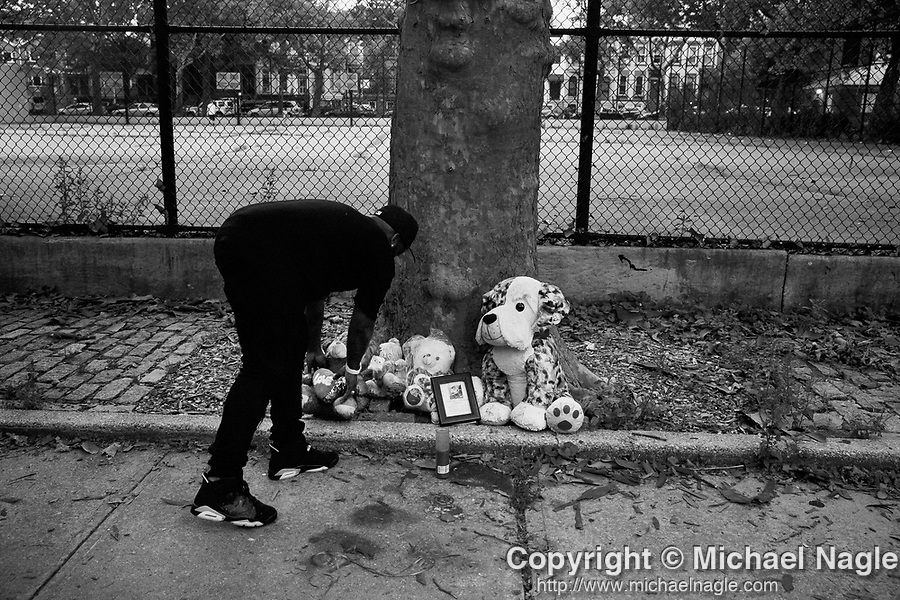 BROOKLYN, NY — JULY 13, 2021: Stanley, the godfather of 1 year-old Davell Gardner, Jr., who was shot while sitting in his stroller at a barbecue a year ago today, adjusts a memorial at Raymond Bush Playground in Brooklyn, NY on July 13, 2021. Two suspects were charged in May, in what investigators believe to be part of a feud between rival gangs. Photograph by Michael Nagle