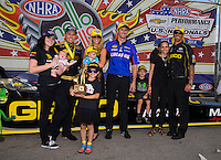 Sept. 1, 2014; Clermont, IN, USA; NHRA top fuel dragster driver Richie Crampton celebrates with daughter Emma Crampton and girlfriend Stephanie Laski and team owner Morgan Lucas with wife Katie Lucas and son Hunter Lucas and crew chief Aaron Brooks after winning the US Nationals at Lucas Oil Raceway. Mandatory Credit: Mark J. Rebilas-USA TODAY Sports