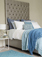 Interior image of a double bed with white linen and blue cushions and blankets on top. A small table with a white lamp is next to it. Styling by Alice King.