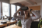 2A1AARP Young creative professional woman using VR headset in an office