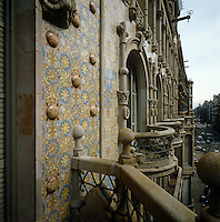 The facade of one of Gaudi's apartment buildings in Barcelona is covered in ceramic tiles detailed with a floral motif