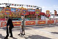 An Hasidic family walk past a fairground ride along the beach in Aberystwyth.