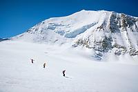 Three women skiing down the Brunegggletscher beneath the Bishorn's northeast face, Switzerland.