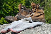 Hiking boots and socks drying on a large rock.