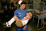 Staff nurse carrying child childrens ward Alder Hey Hospital Manchester NHS 1980s 1988
