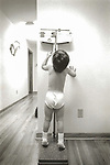 Vintage B&W 84-266 C #14A. Boy on weight scale and measuring height. Scan from print