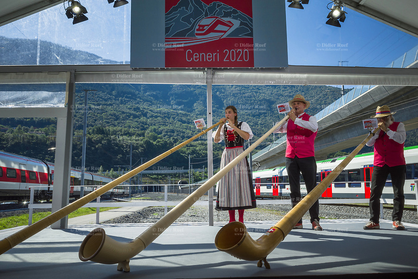 """Switzerland. Canton Ticino. Camorino. Ceneri Base Tunnel (CBT). Official opening ceremony with traditional Swiss Alphorn players. Alphorn is long wooden musical instrument. The alphorn or alpenhorn or alpine horn is a labrophone, consisting of a straight several-meter-long wooden natural horn of conical bore, with a wooden cup-shaped mouthpiece. It is used by mountain dwellers in the Swiss Alps. The Ceneri Base Tunnel (CBT) (Italian: Galleria di base del Monte Ceneri) is a railway base tunnel in Canton Ticino. It passes under Monte Ceneri between Camorino in the Magadino Flat and Vezia near Lugano, and bypasses the former high-altitude rail route through the Monte Ceneri Tunnel. It is composed of two single-track tunnels, each 15.4 km long. It is another part of the New Railway Link through the Alps (NRLA) project. The impact will be significant on international traffic with shorter time trips. The opening of the Ceneri tunnel also means a transport revolution for the southern canton of Ticino. Regional rail lines will be upgraded, and some reckon the change could lead to the creation of a """"Ticino City"""" – one big urban sprawl across the canton. 4.09.2020  © 2020 Didier Ruef"""