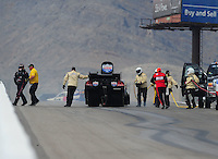Apr. 2, 2011; Las Vegas, NV, USA: NHRA funny car driver Brian Thiel is helped away from his car by safety personnel after a fire during qualifying for the Summitracing.com Nationals at The Strip in Las Vegas. Mandatory Credit: Mark J. Rebilas-