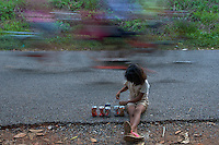 Young girl collecting and playing with empty softdring cans along the road near Phnom Sampeou,rural Battamabang area Cambodia
