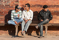 Nepal, Patan.  Three Young Nepalese Men Sitting on a Bench in Durbar Square, Wearing Western Clothes.