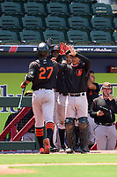 FCL Orioles Orange Moises Ramirez (27) high fives Ricardo Castro (10), Leonel Sanchez (56), and Ricardo Rivera (17) after hitting a home run during a game against the FCL Braves on July 22, 2021 at the CoolToday Park in North Port, Florida.  (Mike Janes/Four Seam Images)