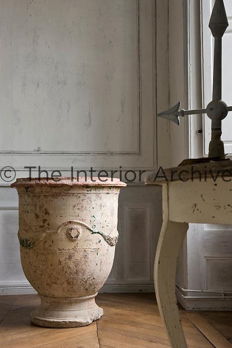 A terracotta urn stands in a corner of the salon